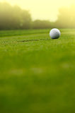 In the hole. Close up of a golf ball close to the hole Stock Photo