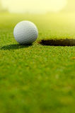 In the hole. Close up of a golf ball close to the hole Stock Image