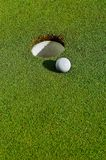 Into the hole. Close up of a golf ball on the grass close to the hole Royalty Free Stock Images