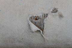 Hole on the clothes. Hole on old faded fabric as background Royalty Free Stock Image