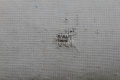 Hole on the clothes. Hole on old faded fabric as background Stock Image