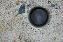 Hole in a concrete fence. Stock Photos
