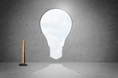 Hole in concrete wall, form of light bulb, made by hammer, which is placed near. Idea concept Royalty Free Stock Photos