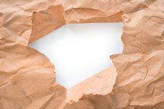 Hole into craft paper, white center isolated. Hole into brown craft paper sheet with torn edges. White center isolated, clipping path included Royalty Free Stock Images