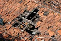 Hole in Damaged Tiled Roof. Hole in damaged clay tiled roof with wooden frame of a traditional building Royalty Free Stock Photography