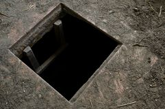 Hole in floor of old house leading to cellar. A square hole in the dirty floor of an abandoned wooden house leading deep into dark cellar. Horror, terror stock photo