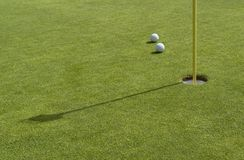 Hole and golf balls in green back Stock Photos
