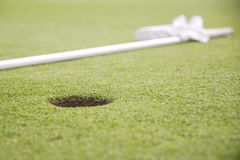 Hole on green of golf course Stock Photos