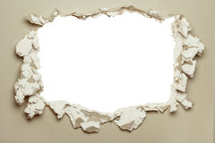 Hole in the grey plasterboard. Hole in the grey plasterboard with uneven edges Stock Photos