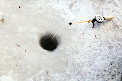 Hole in the ice for winter fishing and a fishing rod with a reel and fishing line and bait. Concept for male hobby or sport, stock photography