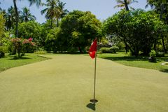 Hole marked with red flag at the golf area. At Maldives Stock Photo