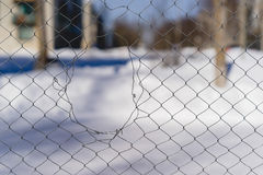 A hole in the mesh fence Stock Image