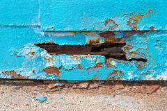 A hole in metal sheet iron blue. Royalty Free Stock Images