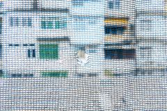 Hole on middle of blue slan shade net. With view of other house stock images