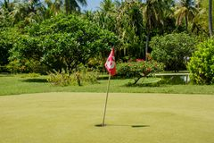Hole number 3 with red flag at the mini golf field. Hole number 3  with red flag at the mini golf playground at Maldives Stock Image