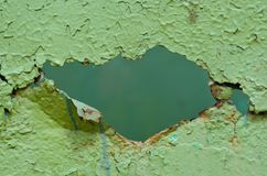 Hole in old green metal wall. Hole in old metal wall painted green. Peeling paint, rust, many old layers Royalty Free Stock Photos