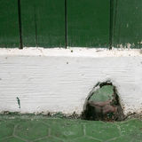 The hole in old white and green wooden wall Stock Photography