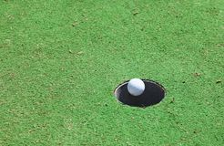 Hole in one. A golf ball on the green , hole in one Royalty Free Stock Image