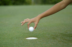 Hole-in-one. Hand dropping a golf ball into the hole Stock Images