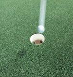 Hole in one med golfboll på hastighet Royaltyfri Fotografi