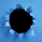 Hole on paper. Peek through a hole on blue paper Stock Photography