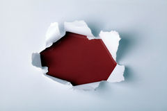 hole in paper with red background inside Stock Images