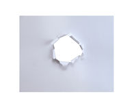 Hole in the paper with torn sides. Royalty Free Stock Photography