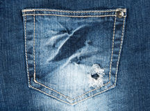 Hole in a pocket of old jeans Stock Photography