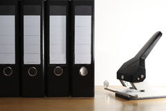 Hole punch. Office hole punch and black file folders Royalty Free Stock Photo
