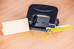 Hole punch and extruded paper smiles on the table. With empty paper card Stock Photography