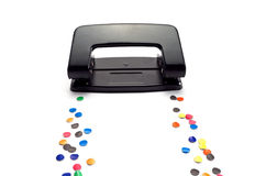 Hole puncher. Hole puncher leaves a trail of colored circles, on white Royalty Free Stock Photography