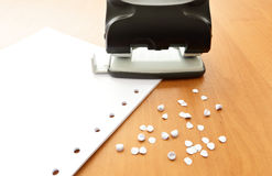Hole puncher with paper and confetti. On the office table Stock Images