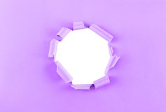 Hole in purple paper Stock Images