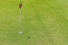 Hole at putting cup hold showing number one pin at outdoor pract Stock Photography