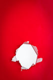 Hole in red paper background. Close up of exposed white hole torn in red background Stock Photos