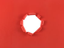 Hole in red paper. Ripped hole in red paper isolated over a white background Royalty Free Stock Image