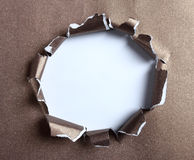 Hole ripped in brown paper Royalty Free Stock Photos