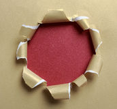 Hole ripped in gold paper Stock Photos
