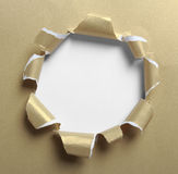 Hole ripped in gold paper Stock Photography