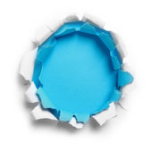 Hole ripped in white and blue paper Stock Images