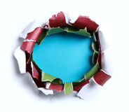Hole ripped in white paper with red and green paper Royalty Free Stock Images