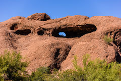 Hole-in-the-Rock. Phoenix, Arizona, USA - A couple enjoys the scenery from the mouth of Hole-in-the-Rock, a natural red sandstone formation in Papago Park once Royalty Free Stock Images