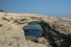 Hole in the rock. Views of the bay through a cove on Donoussa  island in Greece Stock Photos