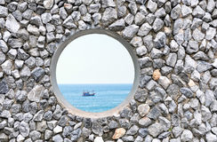Hole  on the rock wall. With ocean background Stock Images