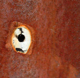A hole on rusty metal sheet Stock Image