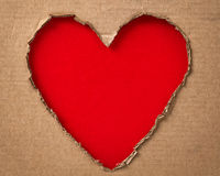 Hole in a shape of heart on cardboard Stock Photography