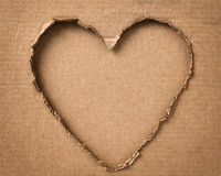Hole in a shape of heart on cardboard Royalty Free Stock Photos