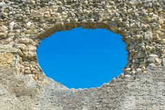 A hole in the stone wall and the blue sky in the background, a ruined wall with a hole. royalty free stock images