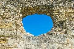A hole in the stone wall and the blue sky in the background, a ruined wall with a hole. stock photo