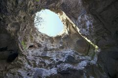 Hole on the top of the cave. Huge cave from inside with a large hole on the top Royalty Free Stock Photos